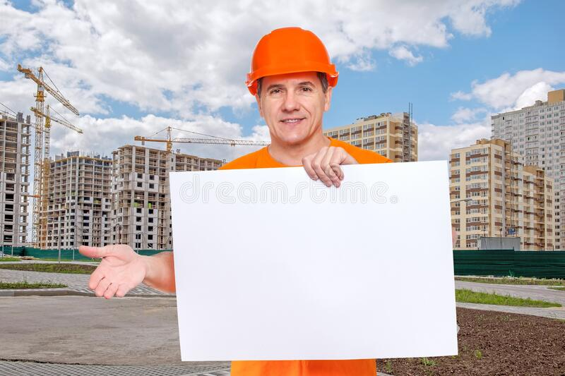 White smiling middle-aged handsome worker wearing orange hard hat, holding blank paper sheet in hand stock photography
