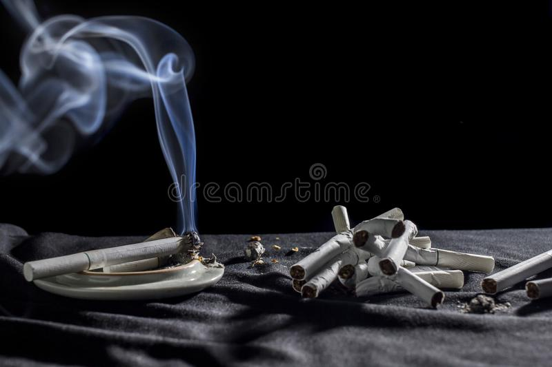A White smoke cigarettes concept abstain from smoking. on black background. White smoke cigarettes concept abstain from smoking. on black background royalty free stock photo
