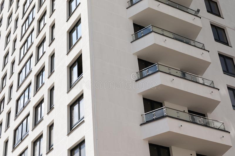 White smooth new modern apartment building facade with windows and balconies, corner of building. View royalty free stock photo