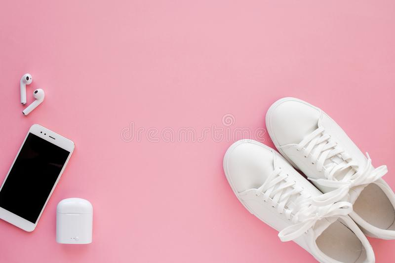 White sneackers, wireless headphones and smartphone are lying on a pink background. stock image