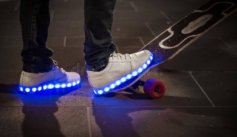 White Sneaker With Led Light on Black and White Long Board royalty free stock images