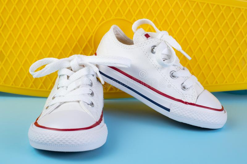 White sneakers in front of skateboard or penny board over blue background. stock photography