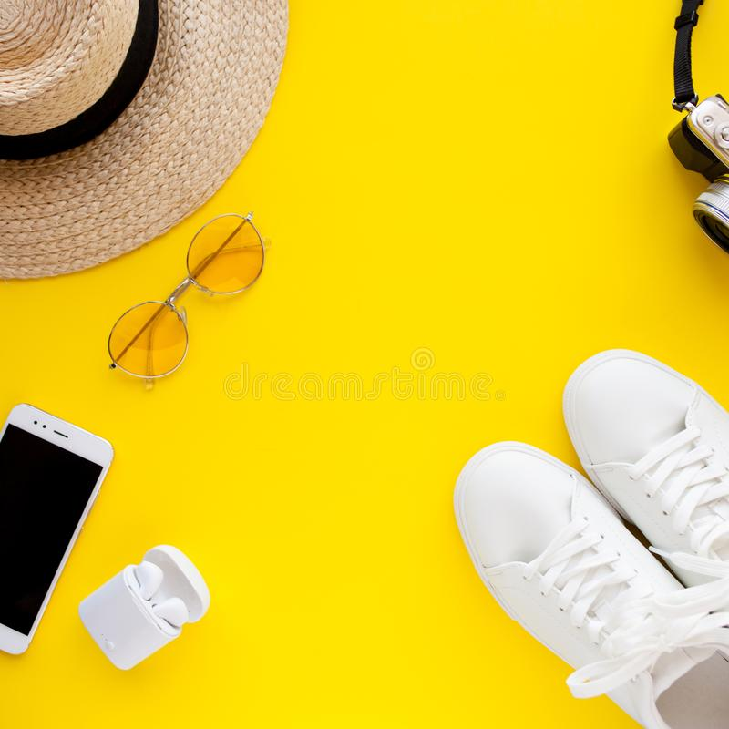 White sneakers, hat, sunglasses, wireless headphones, smartphone and photo camera are lying on a yellow background. stock photos