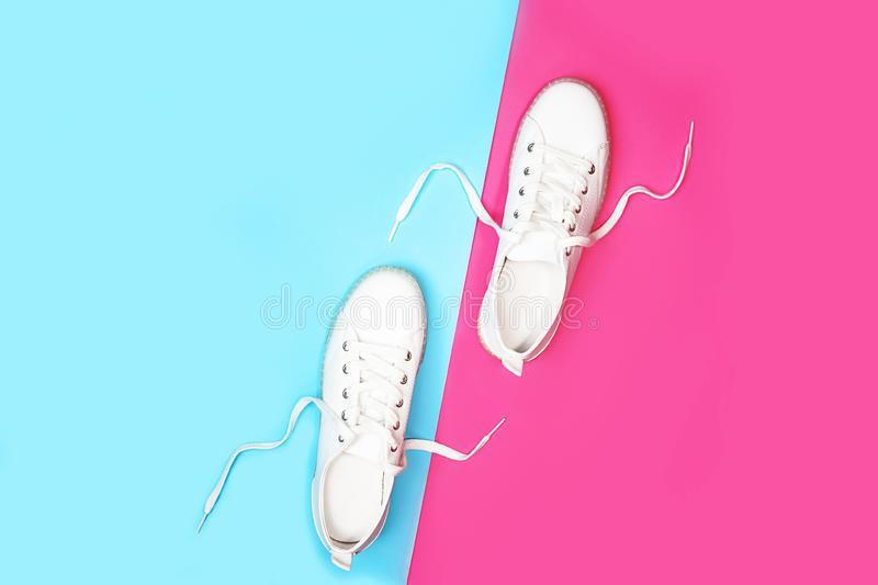 White sneakers are lying on bright neon color blue pink background. royalty free stock photography