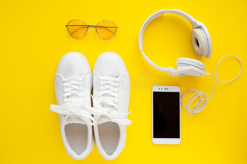 White sneakers, pink sunglasses, white headphones and smartphone are lying on a bright yellow background. stock image