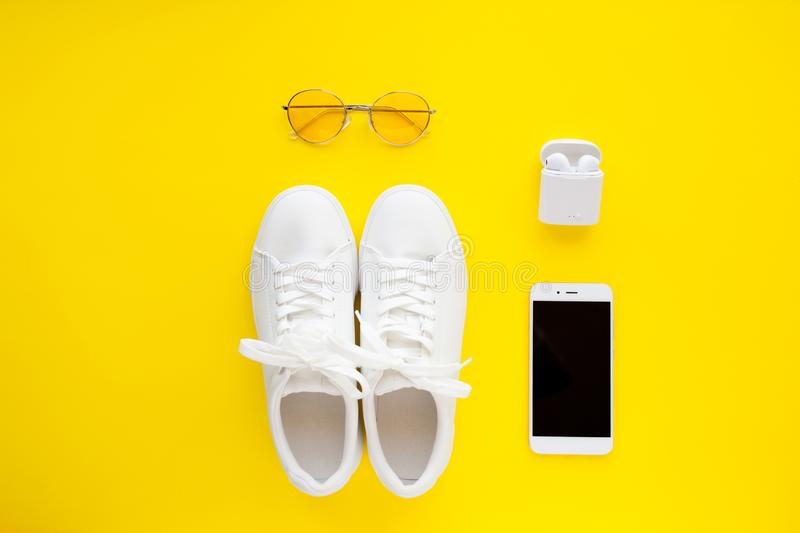 White sneakers, pink sunglasses, white wireless headphones and smartphone are lying on a bright yellow background. stock image