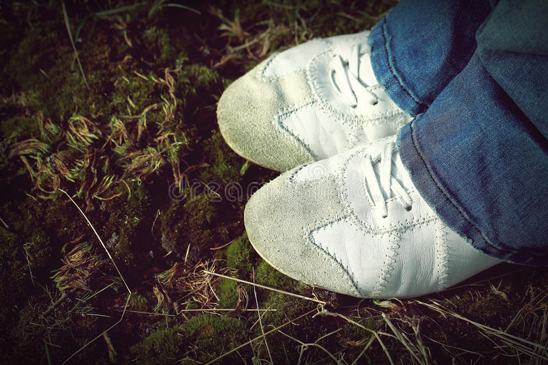 White Sneakers Sport leather shoes walking on moss and grass during sunny day. White Sneakers Sport leather shoes walking on moss and grass. Retro Vintage photo stock photography