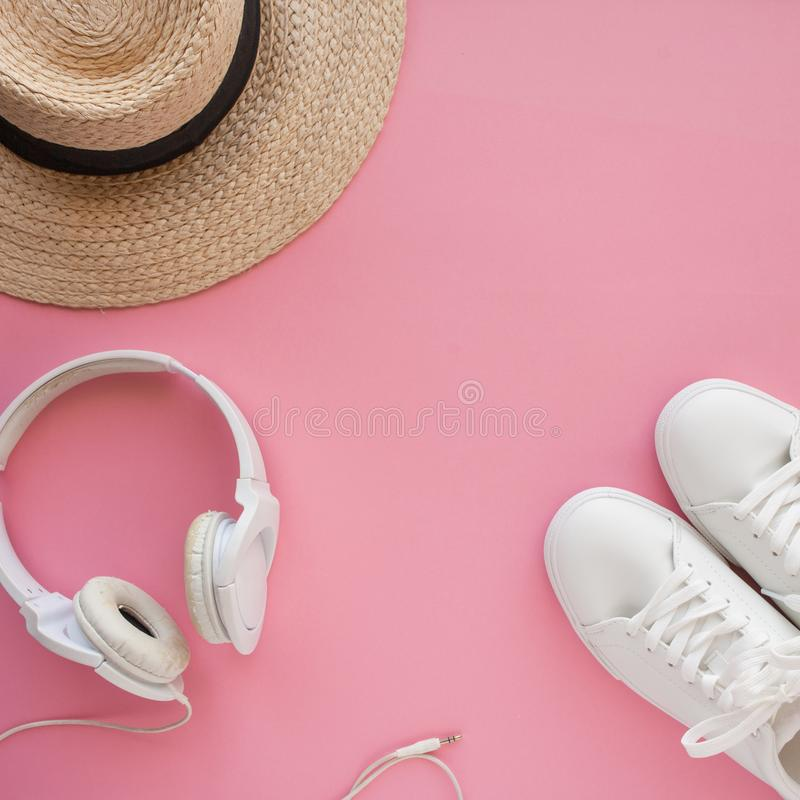 White sneakers, straw hat, headphones, are lying on a bright pink background. stock photo