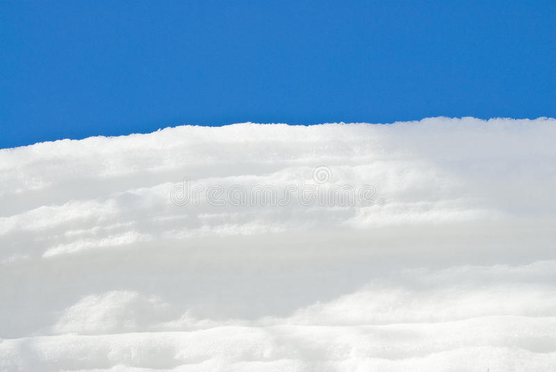 White Snow Against the Blue Sky. A foot accumulation of clean white snow against a deep blue sky stock photography