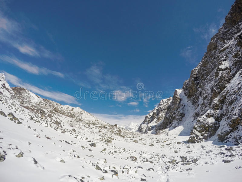 White snow, blue sky and rocky peaks. Nepalese severe winter. Nepal eco travel and extreme sport. Mountain landscape. Trek to mountain Sagarmatha. National Park stock photography