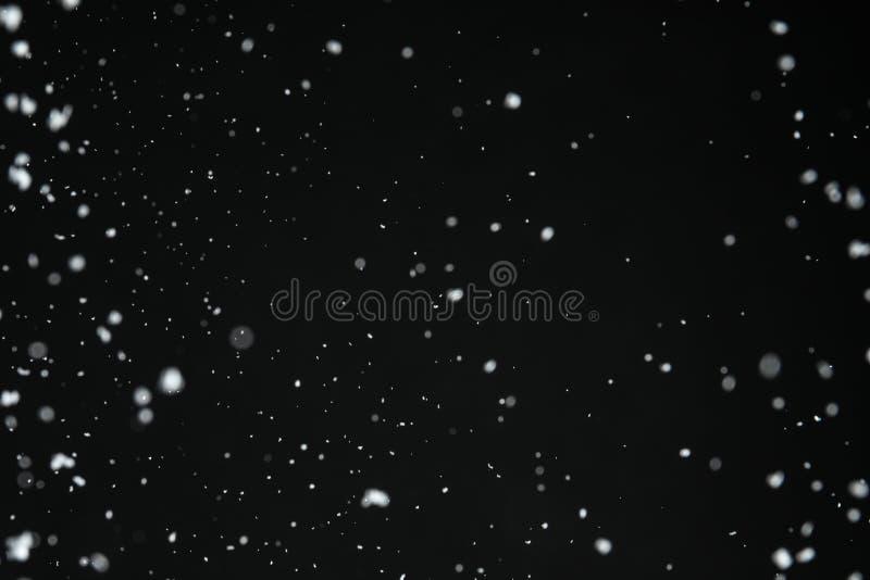 White snow falling down on background. White snow falling down on black background royalty free stock photo