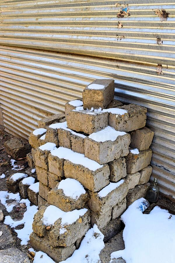 White Snow over Bricks with Closed Shutter of Shop - Snow Fall in Winter in Himalaya - Lockdown in Coronavirus Epidemic royalty free stock photos