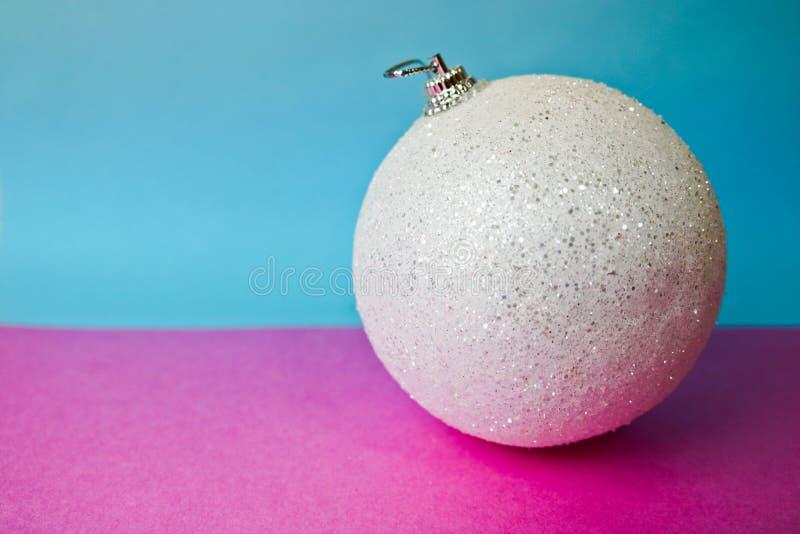 White snow small round xmas festive Christmas ball, Christmas toy plastered over sparkles on a pink purple blue background. White snow small round glass plastic stock photos