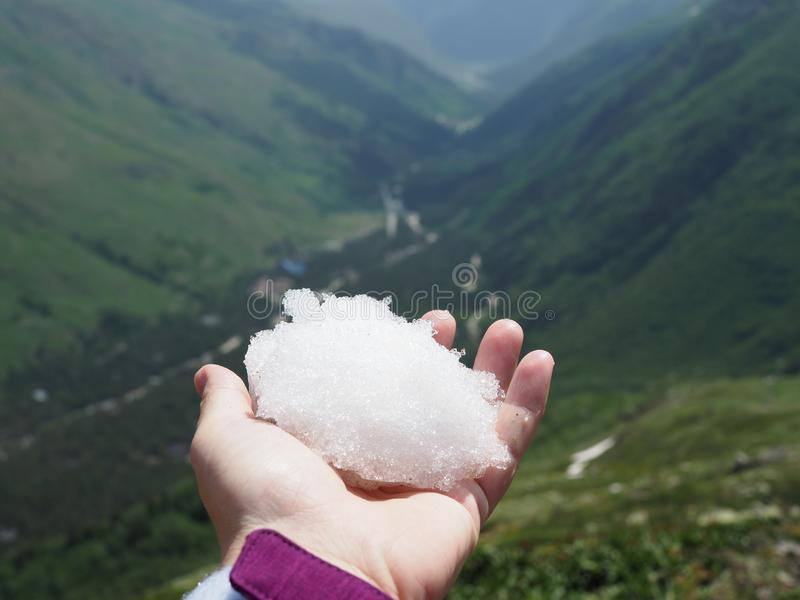 White snowball in hand on a background of picturesque mountains on a Sunny summer day royalty free stock photography