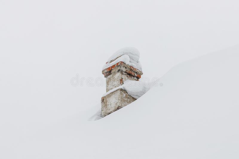 Snowed chimney on rooftop of house in winter. White snowed chimney on rooftop of house in winter stock images