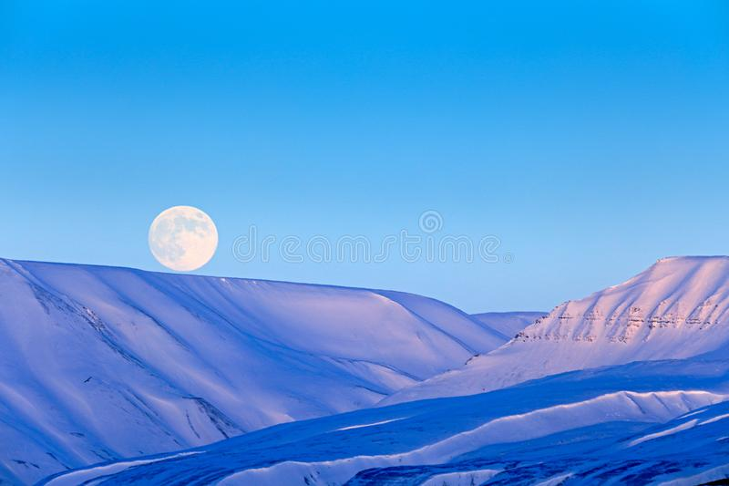 White snowy mountain with Moon, blue glacier Svalbard, Norway. Ice in ocean. Iceberg twilight in North pole. Pink clouds with ice. Floe. Beautiful landscape royalty free stock photos