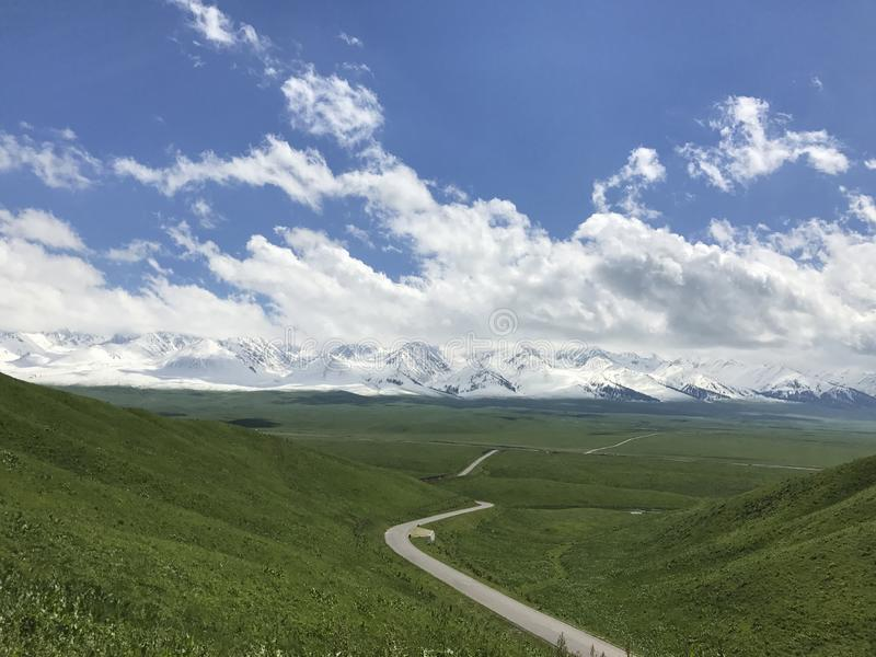 White snowy mountains and grasslands. The clear blue sky is crystal clear, the white clouds are soft and light, the snow-capped mountains have a silver-like royalty free stock photo