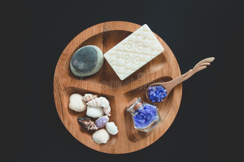 White soap, seshels, bottle, lavender salts and wooden spoon on the wooden round form. Black background. Spa concept royalty free stock photography