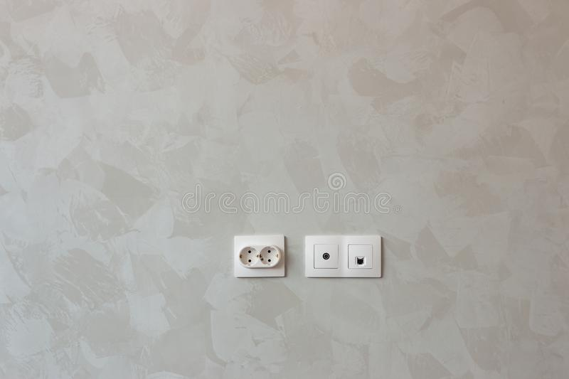 White sockets and switches on the wall being repaired stock photography