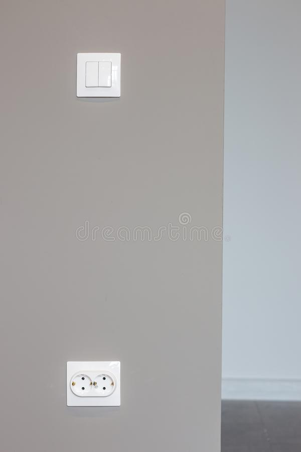 White sockets and switches on the wall being repaired stock image