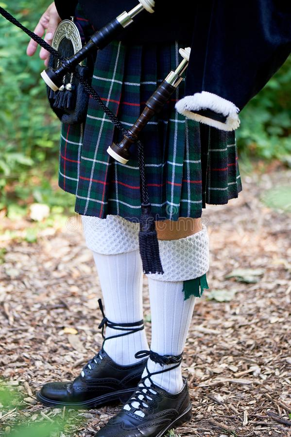 White socks. A man with a bagpipe, a kilt in a cage with a green and red stripe.Culture. The details of the skirt of the. White socks.A man with a bagpipe, a royalty free stock photos