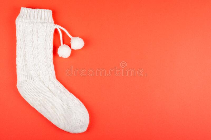 White socks with pom poms on red background composition. Flat lay and top view photo with copy space royalty free stock image