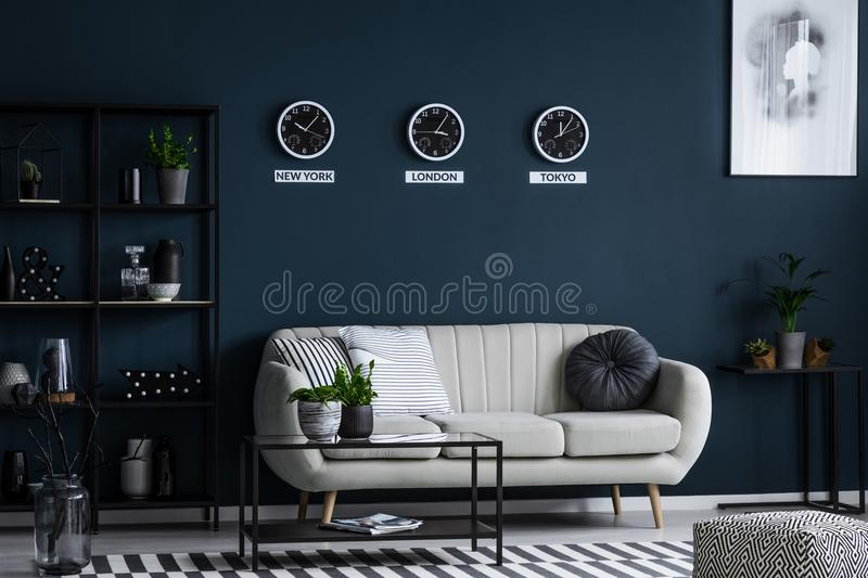 White sofa, coffee table, metal shelf with decorations and three stock image