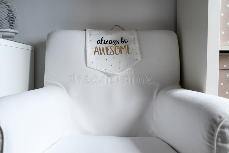 White sofa with funny sayings. always be awesome.  stock photography