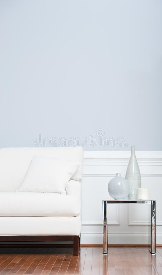 White Sofa and Glass End Table Against Blue Wall. White sofa and glass end table with vases set against pale blue wall. Vertical shot stock photography