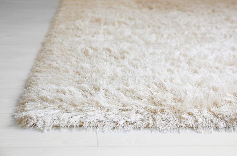 White soft carpet on wooden floor,. Closeup stock photography