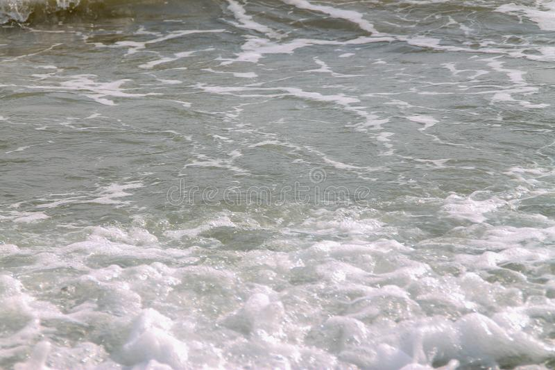 White soft wave rolling splash on empty tropical sandy beach in sunny day.  stock image