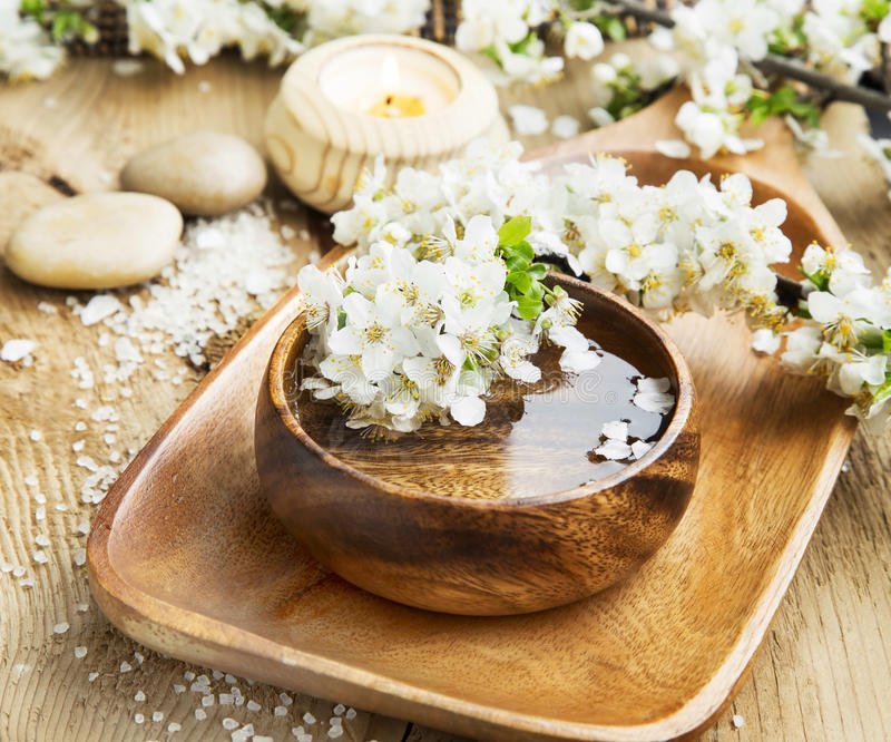 White Spa Flower Blossom in a Wooden Water Bowl.Beautiful Spa Tr. Spa White Flowers Blossom with Wooden Water Bowl on Wooden Background.Wellness and Spa stock images