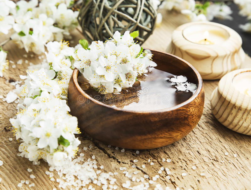 White Spa Flower Blossom in a Wooden Water Bowl.Beautiful Spa Tr. Spa White Flowers Blossom with Wooden Water Bowl on Wooden Background.Wellness and Spa stock photo