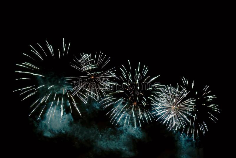 White sparks of a festive fireworks and blue smoke royalty free stock images