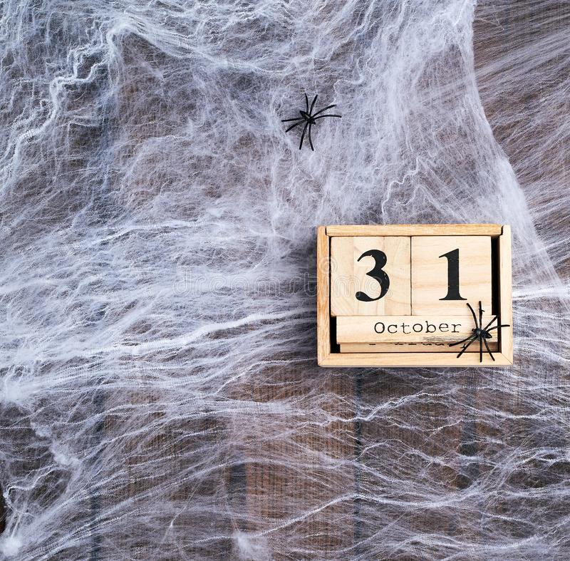White spider web and wooden retro calendar made of blocks with the date of October 31 stock image
