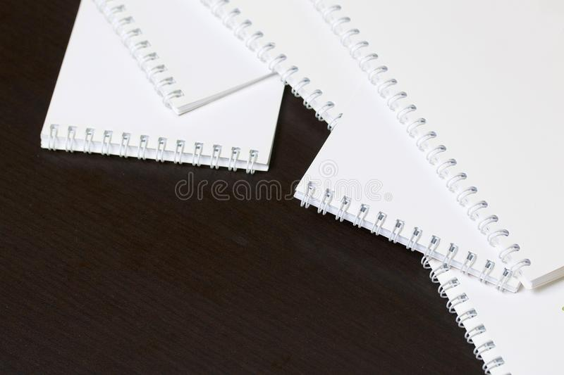 White spring notebooks for notes and sketches. Stationery for school and teaching. On a dark background. stock photography