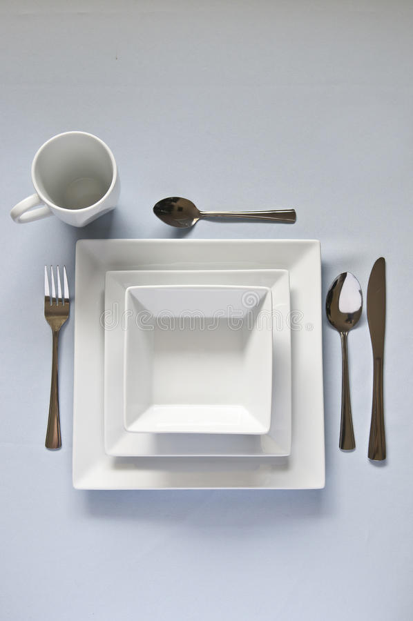 White, square dinner set with cutlery. royalty free stock image