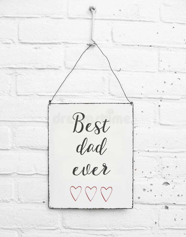 White square metal plate on white bricks background - with text happy fathers day for the best dad in de world and red hearts stock photo