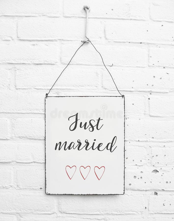 White square metal plate on white bricks background - with text just married for love couples and weddings stock image