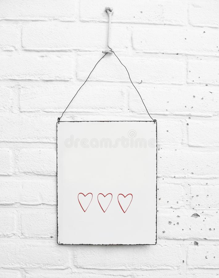 White square metal plate with cute red hearts and space for own text on white brick background stock photo
