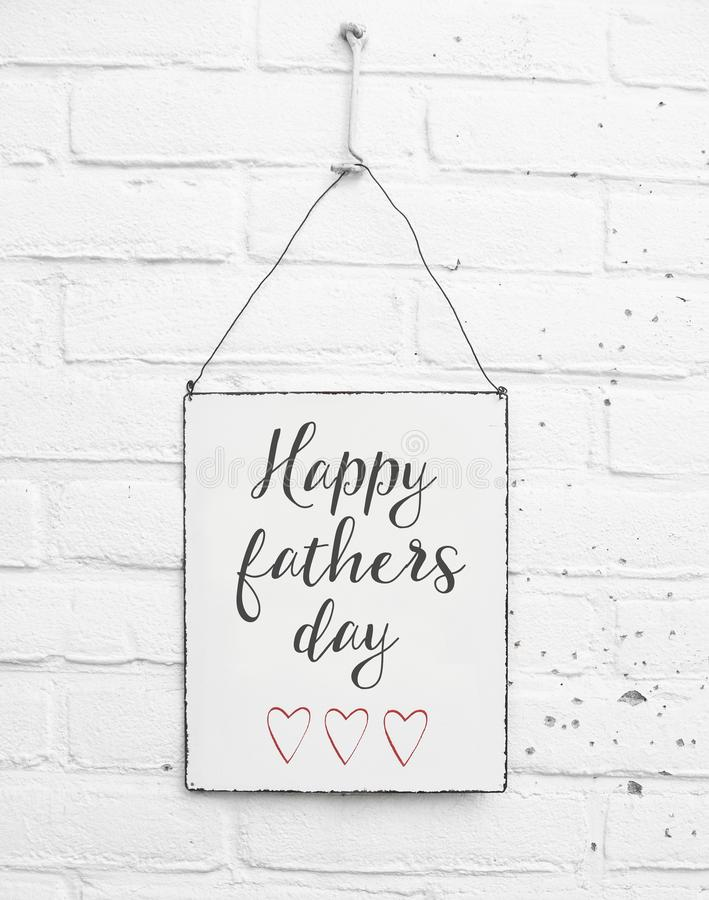 White square metal plate on white bricks background - with text happy fathers day for the best dad in de world royalty free stock photo