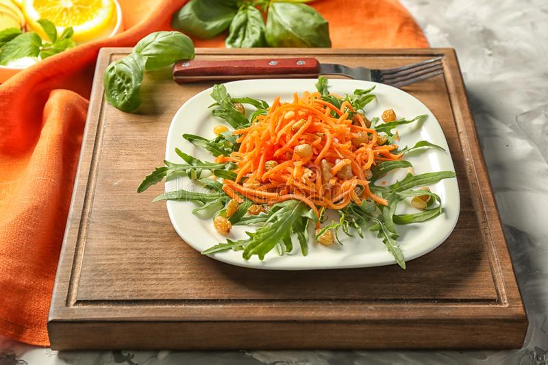 White square plate with delicious carrot raisin salad with green stock photo