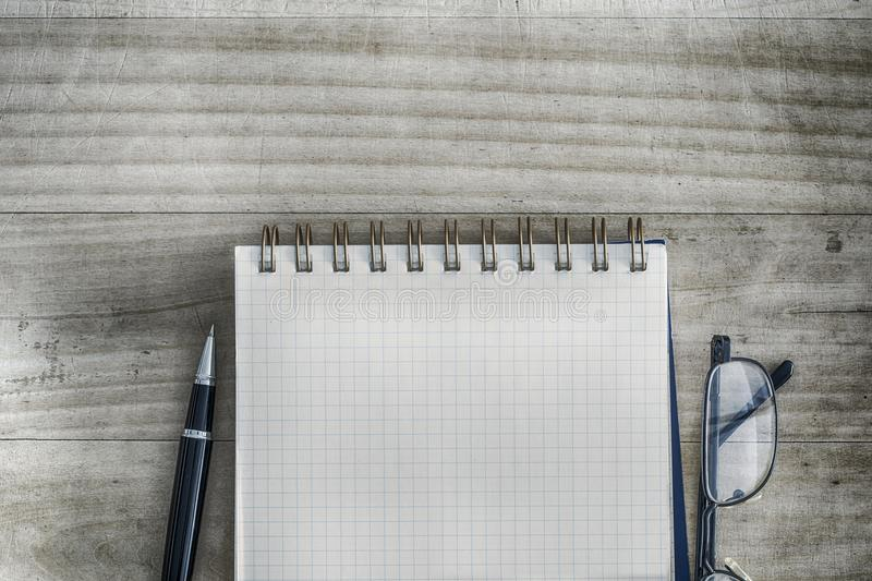 White square spiral notebook next with pen and eyeglasses on the table royalty free stock photo