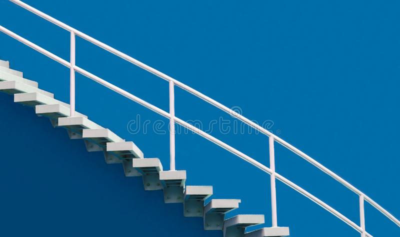 White staircase on blue background. White stairs and handrail on blue background , steps for success stock photos