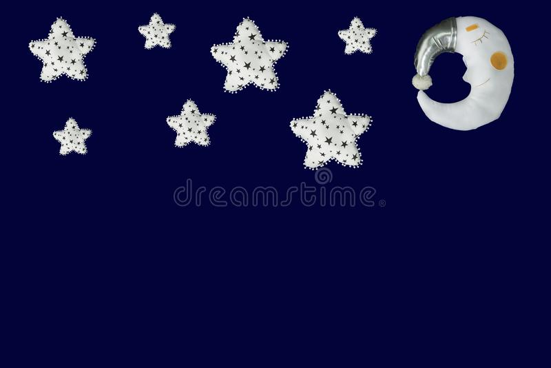 White stars and sleeping moon in silver bonnet on navy blue background.  stock photo