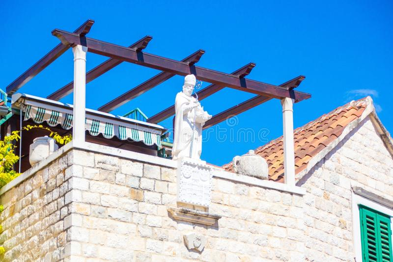 White statue of a man with a shiny iron stick on the roof of a house in the centre of the old town of Split, Croatia. Diocletian Palace royalty free stock photo
