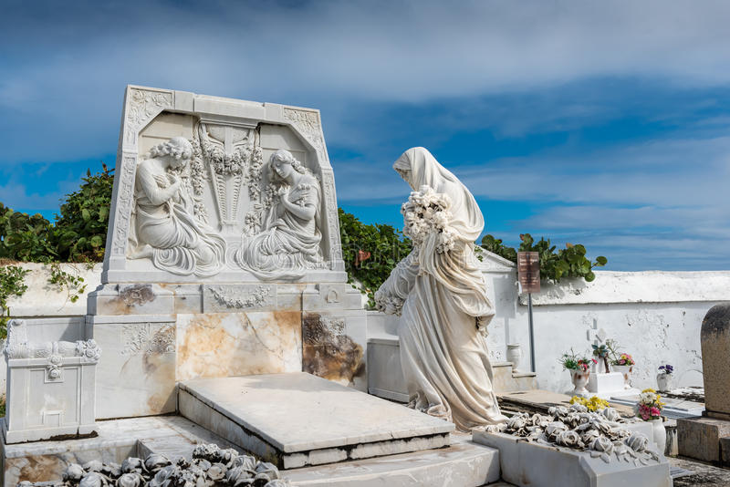 White statue of a women standing near a grave. With large head stone with two other women carved into stone royalty free stock photography