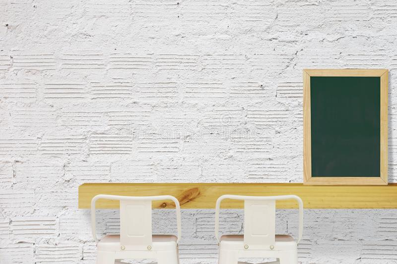 Steel Stools with Wooden Shelf and Blank Black Chalkboard on White Brick Wall Background stock images
