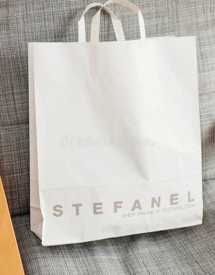 White Stefanel Fashion bag on armchair. PARIS, FRANCE - OCT 24, 2016: White shopping bag with Italian fashion brand STEFANEL logotype on the armchair royalty free stock photography