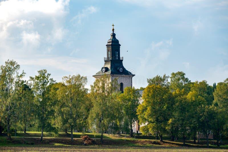 White stone church with autumn colored surrounding trees stock photo